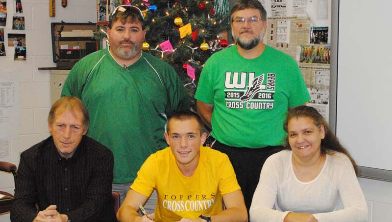 Daily Leader / MARTY ALBRIGHT / West Lincoln's Jason Watts signs a cross-country scholarship with the Blue Mountain College Toppers. Pictured with Jason is his father Gary Watts (left) and his mother Angie Watts (right); (standing from left) West Lincoln Athletic Director Charlie Jackson and Head Cross-Country Coach Greg Allen.