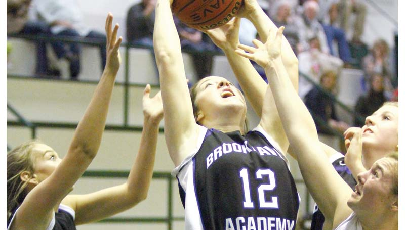 Daily Leader / Sherylyn Evans / Brookhaven Academy's Kailyn Jordan (12), Sissy Byrd and Anna Michael Smith battles for the rebound against Central Hinds' Madison Curtis (21) Saturday night.
