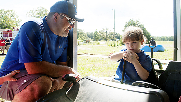 Photo by Julia Miller / Chris Reed talks to Gabe Albritton a few days after the boy was rescued from a well on Labor Day. Reed gives back to his community through his volunteer service with the Hog Chain Volunteer Fire Department.