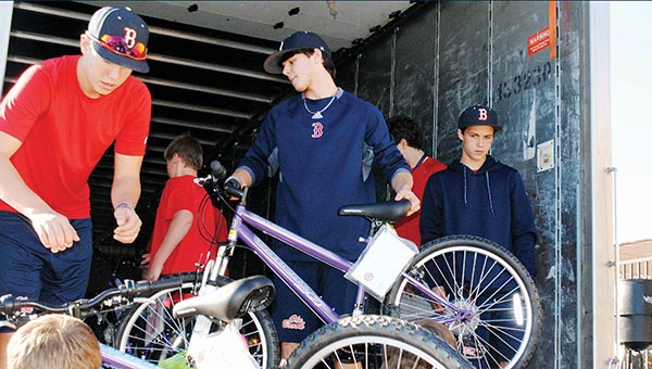 Photo by Aaron Paden/ The Brookhaven High School baseball team, overseen by coach Randy Spring, loads a truck with 285 bicycles Monday at the Wal-Mart distribution center. The bicycles are being given to Junior Auxiliary's annual Wish Tree project by an anonymous donor.