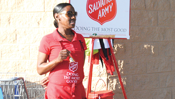 Photos by Aaron Paden/ Above, bell ringer Rockie Bannister stands by the Wal-Mart entrance greeting customers Tuesday. Below, a Wal-Mart customer donates a few dollars to the Salvation Army Tuesday.
