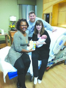 Rita Robinson, left, presents Mike and Rachel Powell and their son, James Robert Powell, with a book from the Cuddle Up program.