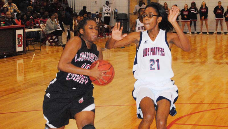 Daily Leader / Marty Albright / Lawrence County's Zipporah Baylis (left) drives to basket to score a layup against Brookhaven's Arnancy Arnold (21) in girls action Saturday night.