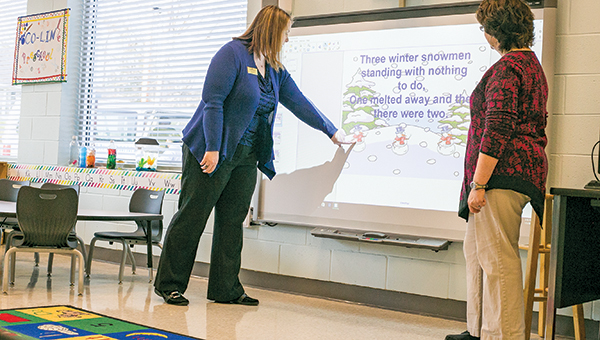 Photo by Kaitlin Mullins / Dean Jackie Martin (left) and preschool teacher Melissa Kyzar check out the educational games that children at the Copiah-Lincoln Early Childhood Education facility enjoy playing on the new smart board. The new facility was finished in November.