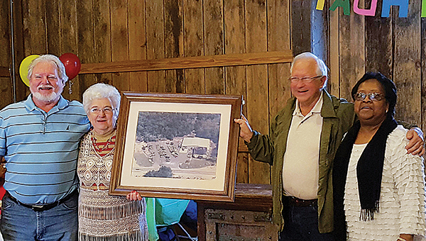 Photos submitted / Ed Tinsley receives an aerial photo of Mr. T's Apparel building at his 72nd birthday celebration, which included a reunion of his former employees. Pictured are Ken Meridith, Bonnie Chance, Tinsley and Maggie Ruth Robinson.