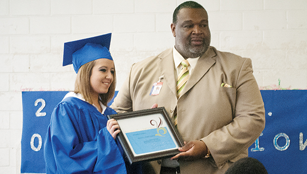 Photos by Julia Miller / Kristen Kirton , left, is only the second person to graduate from the GED program at Fannie Mullins School. Deputy Superintendent Rod Henderson presents her certificate at a recent graduation ceremony.