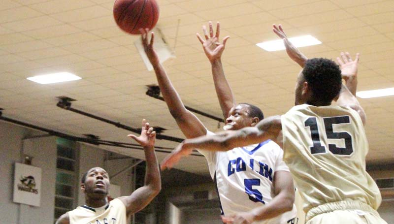 Co-Lin Media / Natalie Davis / Co-Lin point guard Jonathan Dalton (12) splits the East Central defense of Keion Peoples (11) and Prince McDaniel (15) Thursday night.