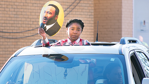Photos by Kaitlin Mullins / Above, a young lady peeks from a sunroof holding a photo of Dr. Martin L. King Jr. Drive during the Sunday parade. Brookhaven Police Chief Bobby Bell led the convoy, followed by fire trucks and parade organizer Bernetta Character followed in the last vehicle in the parade. Left, a young man joins a pack of motorcyclists in the parade honoring Martin Luther King Jr. that made its way through downtown Brookhaven on Sunday.