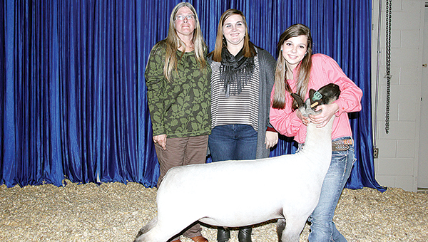 Photo by Alex Jacks / Supreme champion market lamb, Rachel McDaniel and her buyers pose after the Sale of Champions Monday night.