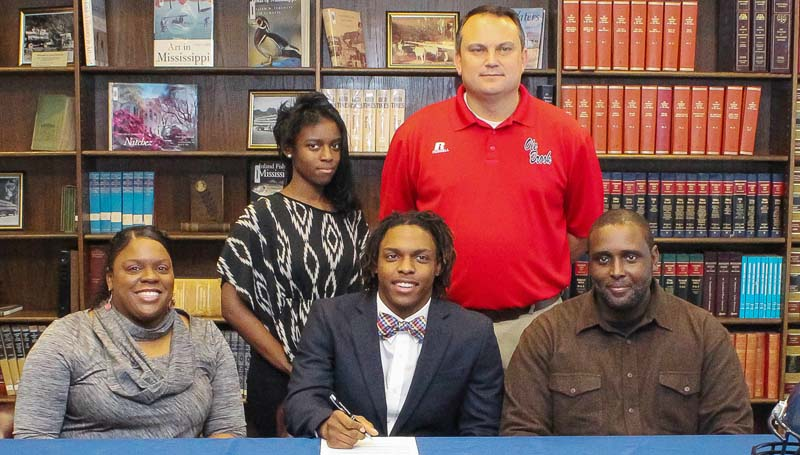 Daily Leader / April Clopton / Brookhaven's Willie Bates has signed to play football with the Gulf Coast Community College Bulldogs. Pictured with Bates are his parents Monica Bates and Willie Bates Jr. Standing are his sister Abi Bates and Brookhaven head coach Tommy Clopton.