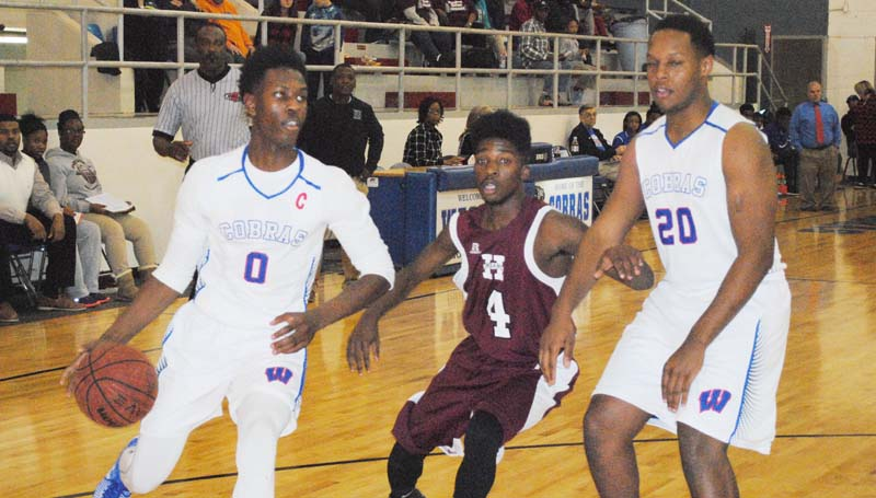 Daily Leader / Marty Albright / Wesson's Anthony Jones (0) drives to the basket as teammate Kendrick Brown (20) sets a block against Hazlehurst's ZyQuaris Watkins (4) Thursday night at the Snake Pit.