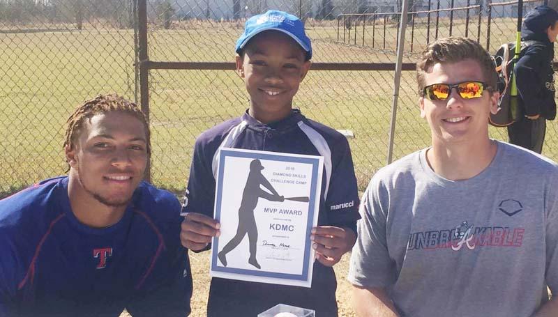 Daily Leader / Photos by James O. Covington / Donovan Moore receives the KDMC MVP Award at the Franklin County Diamond Skills MLB Kids camp by Texas Rangers' Ledarious Clark and Atlanta Braves Bradley Roney.