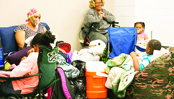 Photo by Kaitlin Mullins / Leticia Coleman (left) and Ann Moore (right) gathered with relatives in anticipation of Tuesday's weather at the FEMA building. Coleman and Moore, both of whom live on Industrial Park Road, said they weren't taking any chances, especially losing power. About a dozen people took shelter there.