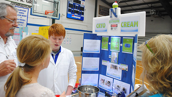 McLaine Boyd, right, stands with his science project Monday following his first place win in the seventh-eighth grade biochemistry division of Brookhaven Academy's science fair. Boyd's project was to use nitrogen to make ice cream. Boyd, along with 76 other first and second place winners from BA, will advance to the Mississippi Association of Independent Schools District 4 West Science Fair on March 23.