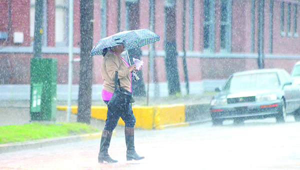 Photo by Luke Horton / A woman crosses Whitworth Avenue during heavy rainfall Friday morning.