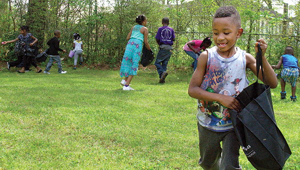 Photo by Aaron Paden / DJ Smith races for Easter eggs at the Kynett United Methodist Church Saturday. The church also served hotdogs and hosted local hip-hop group #TEAMBROKE at the event.