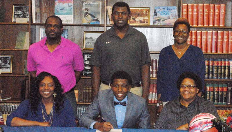 Daily Leader / Marty Albright / Brookhaven's Lazorian McNulty has signed basketball scholarship with the Co-Lin Community College Wolves. Pictured with McNulty is his mother Jonnell Smith (left) and his grandmother Margaret McDaniel. Standing is Standing is Brookhaven girls coach Preston Wilson, Brookhaven boys basketball coach Jimmie Butler and grandmother Lisa Chatman.