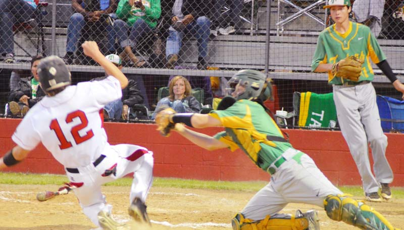Daily Leader / Chris King / Loyd Star's Konner Allen slides into home plate safely as Taylorville catcher Kenner Todd reaches to make a play at Smith Field.