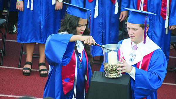 Photo by Julia Miller / Brookhaven High School student council president Jaylynn Thompson and Fellowship of Christian Athletes president Taylor Pendley light a candle in honor of Nealey Brown during Friday's graduation. Brown, who graduated in December from BHS, died in a car accident earlier this spring.