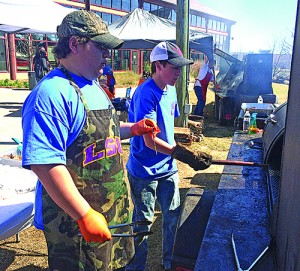 Sam Edwards (left) and Zach Jenkins fire up the smoker during one of the Smokin' Hornets Cooking Team's competitions this year.