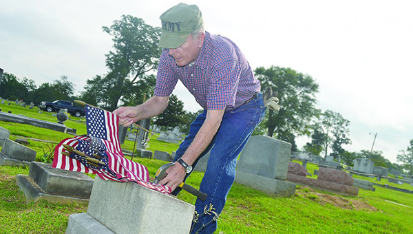 Photo by Donna Campbell/ American Legion Post Commander Keith Reeves and other volunteers gathered at Rose Hill Cemetery Saturday morning to place flags in front of the graves of fallen soldiers for Memorial Day.