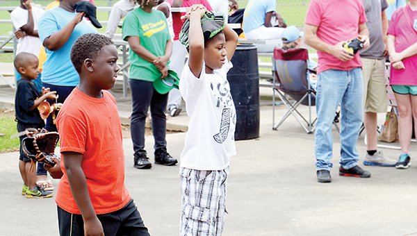 Photo by Donna Campbell / Marco Dunnigan (left) and Tylandis Fields joined dozens of other youth and adults Saturday for the opening day ceremony at the Dr. A.L. Lott Youth Baseball Complex.