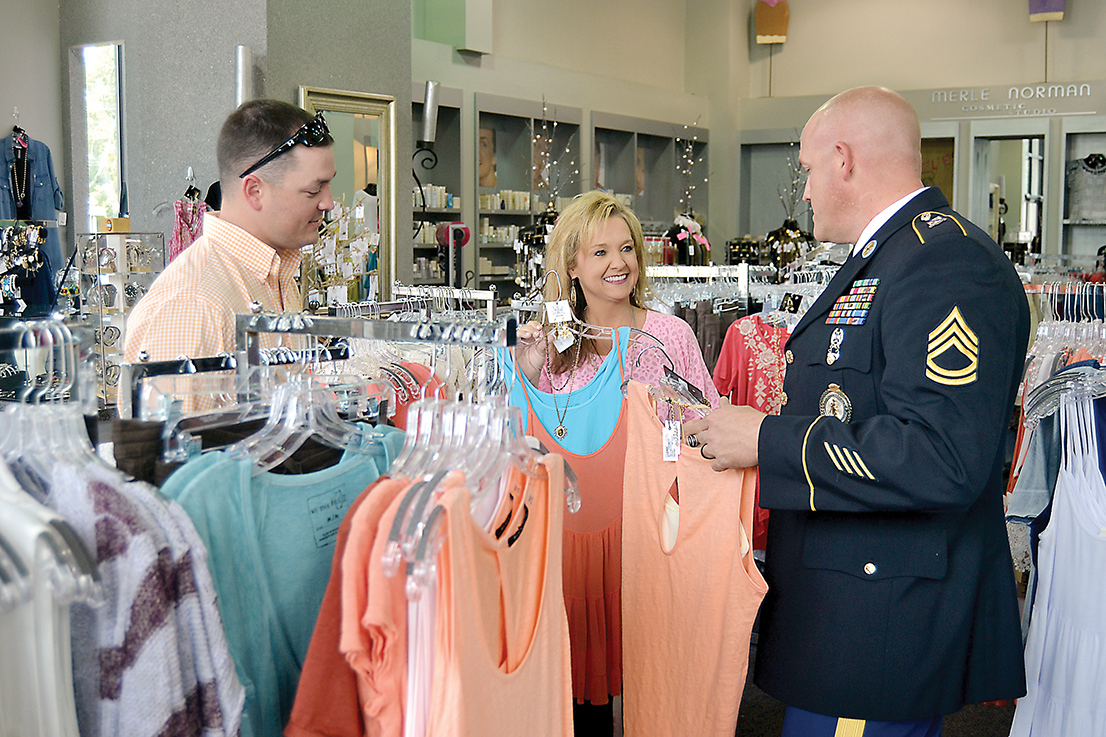 Photo by Donna Campbell/ Joshua Holcomb (left) and Castles owner Cathy Franck help Jason Gaskin decide which outfit to buy for Gaskin's wife. Castles celebrates 25 years in Brookhaven on Friday with giveaways and store specials from 9:30 a.m. to 5 p.m.