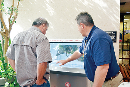 Photo by/Donna Campbell Lincoln County District 4 Supervisor Eddie Brown (at left) watches David Culpepper, marketing director for King's Daughters Medical Center, demonstrate the ease of use of a community health interactive portal that will be available during business hours at the Lincoln County Courthouse. The portal gives individuals access to health information as well as contact information for every medical provider, physicians and nurse practitioner available in the county. The board voted unanimously Monday to accept the portal, which will be maintained by the hospital. A second portal will be placed at Lincoln County Public Library as well as at at least two retail pharmacies.