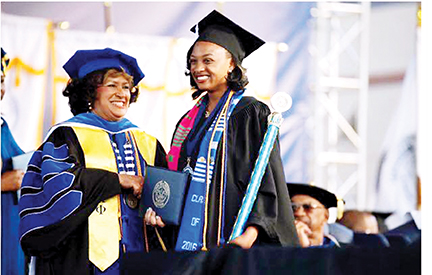 President Carolyn Meyers (left) gives Orionna Brumfield her diploma during commencement exercises at Jackson State University in April. First lady Michelle Obama spoke at that event.