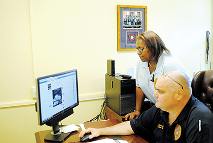 Photo by Aaron Paden/Capt. Clint Earls and Sgt. Penelope Banks go through the department's Facebook page Wednesday as part of their daily schedule in a new effort to connect to the community through social media.