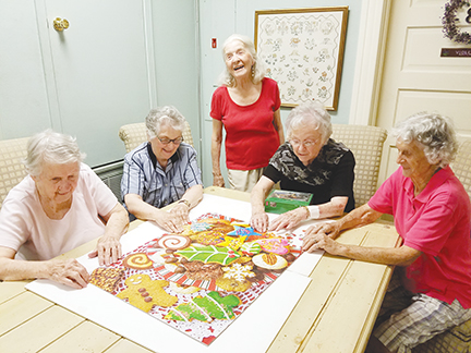 Photo By Donna Campbell/Several retirees often gather on the second floor of The Inez to put together jigsaw puzzles and play bridge. Finishing a puzzle Wednesday are Marian Vivian Morgan (left), Sallie Williford, Betty Jo Smith Barham, Violet Palmer and Marian McMillian.