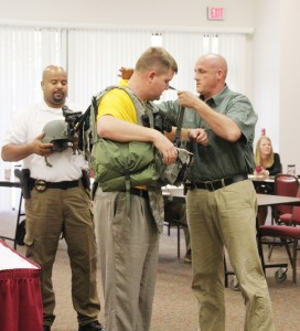 Photo by Alex Jacks/Deputy Jason Gaskin and investigator Damian Gatlin help Rayborn into the bulletproof vest an officer would wear while tracking down an active shooter.