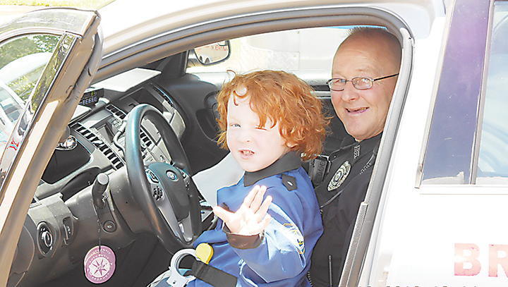 """Photos submitted/Brookhaven Police officer Kevin Thompson lets Caden Hobkirk """"drive"""" his squad car during the boy's recent visit to the station."""