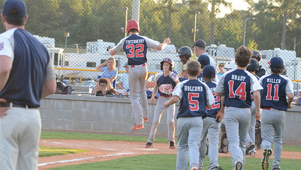 Photo by Anthony McDougle/  Tyler Fortenberry leaps onto home plate after hitting a solo home run in the third inning.