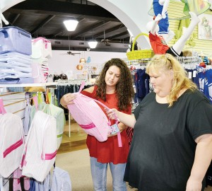 Sales associate Katherine Green helps shopper Dana Rutland pick out a backpack Monday at Expectations on Brookway Boulevard.