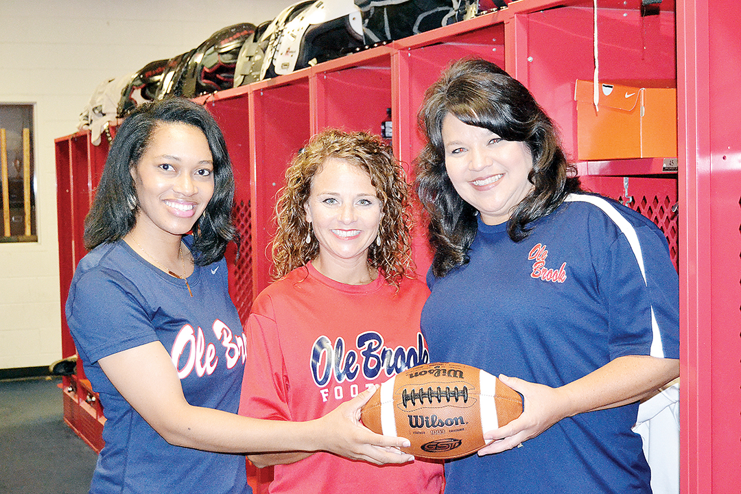 """Photo by Donna Campbell/Coaches' wives Shonique McLaurin (left), Tiffany Bass and April Clopton get ready for the """"Lipstick and Laces"""" ladies-only clinic hosted by Brookhaven High School Saturday beginning at 5:30 p.m. at King's Daughters Medical Center Performance Center. Brookhaven Academy will also host a similar clinic in the cafeteria Monday beginning at 7:30 p.m."""
