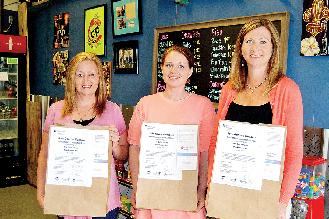 Photo by Donna Campbell/K&B Seafood owner Becky Allen (left), store manager Liz McDaniel and Gentiva Hospice representative Laurie Sullivan show the bags that can be filled with non-perishable goods and personal hygiene items to be donated to Doll's House in Brookhaven.