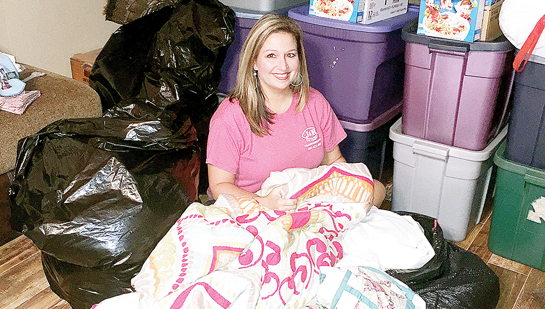 Photo by Amy Rhoads/Aimee Stinson sits among boxes and bags of clothes and supplies donated for her family and their neighbors in South Louisiana, where she's from originally. She said she is thankful for the outpouring of love and generosity she's seen from Lincoln County residents.