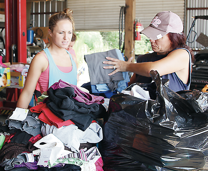 Photo by Alex Jacks/Ashley Martin (left) and Terry McCord sort through bags of clothes at RV Source Tuesday in preparation of sending a trailer of supplies to Denham Springs, Louisiana.