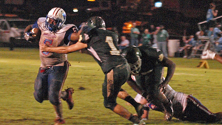 Photo by Tracy Fischer/ Junior Cobra fullback Jerry Barlow stiff arms McLaurin defender Austin Sandifer as he fights for extra yardage.