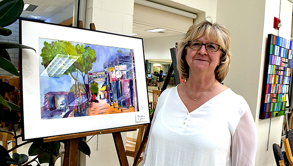 """Photos by Julia Miller / Janet Smith stands next to one of her paintings, """"Downtown at Janie's,"""" during a reception held for the art show on display at the Lincoln County Library. The show includes paintings by Smith and her mother, Billie Mathis. The art remains on display through Tuesday."""