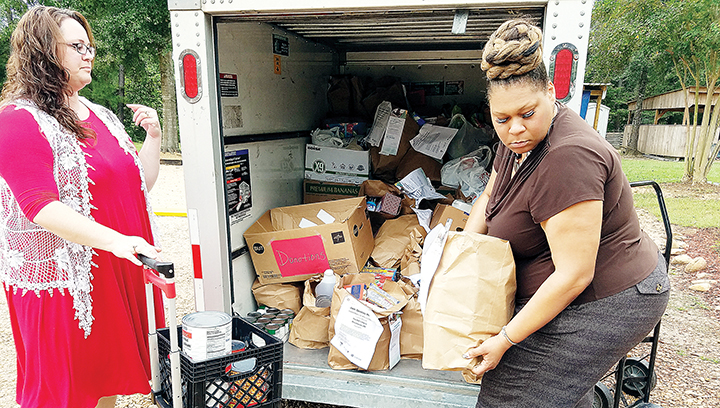 Photo by Donna Campbell/Sara Skinner, a nurse with Gentiva Hospice, (left), and Gentiva Executive Director Erika Newsome help unload some of the 2,673 pounds of food collected in the company's 12th annual food drive. The food was donated to The Doll's House in Brookhaven.