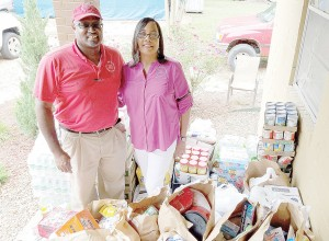 Photo by Donna Campbell/Johnnie and Stephanie Turner, The Doll's House's executive directors, stand amid bags and cases of groceries donated to the organization Tuesday by Gentiva Hospice.