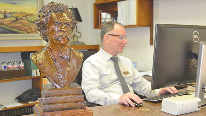 Photo by Donna Campbell/Henry Ledet, director of the Lincoln-Lawrence-Franklin Regional Library System, makes final preparations for an open house to be held Thursday at the Brookhaven main branch at which this bronze bust of Mark Twain, created by the late Bruce Brady, will officially be moved to its new home in the main lobby.