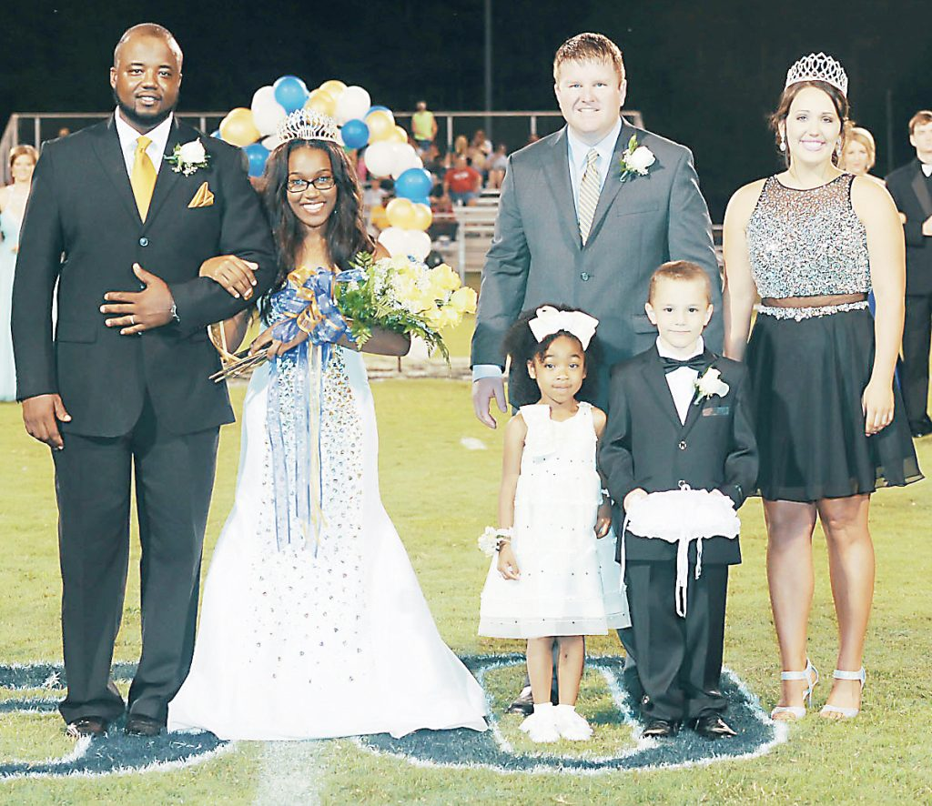 Photo by Teresa Allred Photography/Lamareo Porter (left) escorts Bogue Chitto's 2016 Homecoming Queen Tukiyah Godbolt  onto the school's football field Friday night. Godbolt was crowned with the help of Bogue Chitto's Principal Jay Rayburn, the 2015 Homecoming Queen Brooke Myers, crown bearer Landon Wright and flower girl LaTaysia Felder.