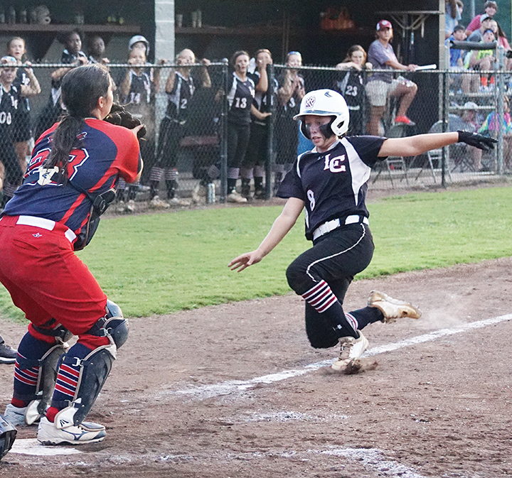 Photo by Jana Harp /Lawrence County's Sydney Pevey attempts to beat the throw home to Ole Brook catcher Meg Foster during the Panthers'  7-5 win over the Cougars in extra innings Thursday night.