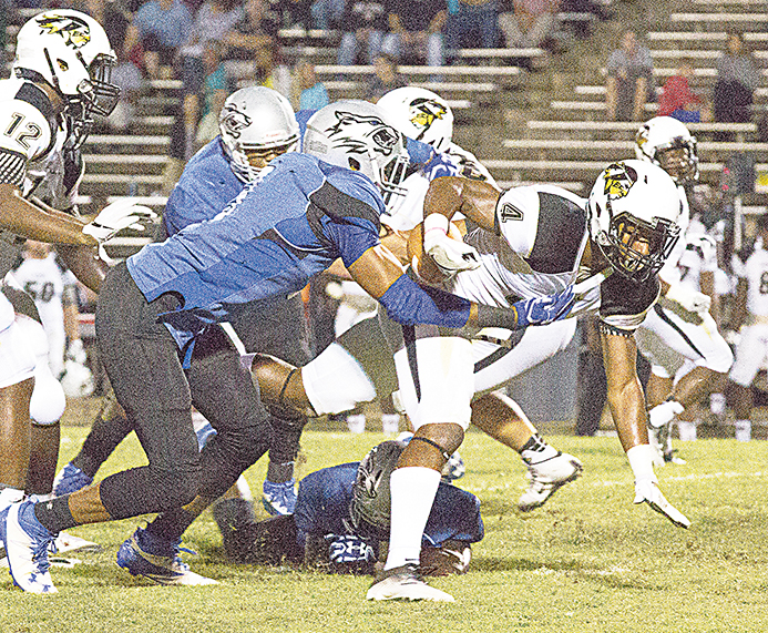 Photo by Amy Rhoads /A Co-Lin defender wraps up East Central's running back during the teams' game Thursday night in Wesson.