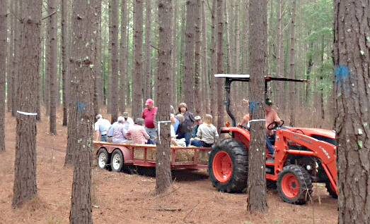Photo submitted/Locals hitch a ride into the forest on a tractor for the 2015 Lincoln County Forestry Association seminars.