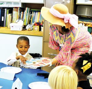 Preschooler Eldiris Long takes a cookie served by teacher Macie Bateman during the elegant elephant party at Mamie Martin Elementary Friday.