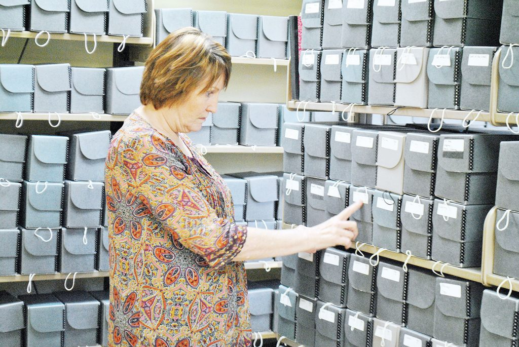 Photo by Aaron Paden/Billie Smith looks over rows of boxes storing hundreds of thousands of photos in the Don Jackson collection at the Lincoln County Public Library Wednesday. Smith said the library is sorting the collection.
